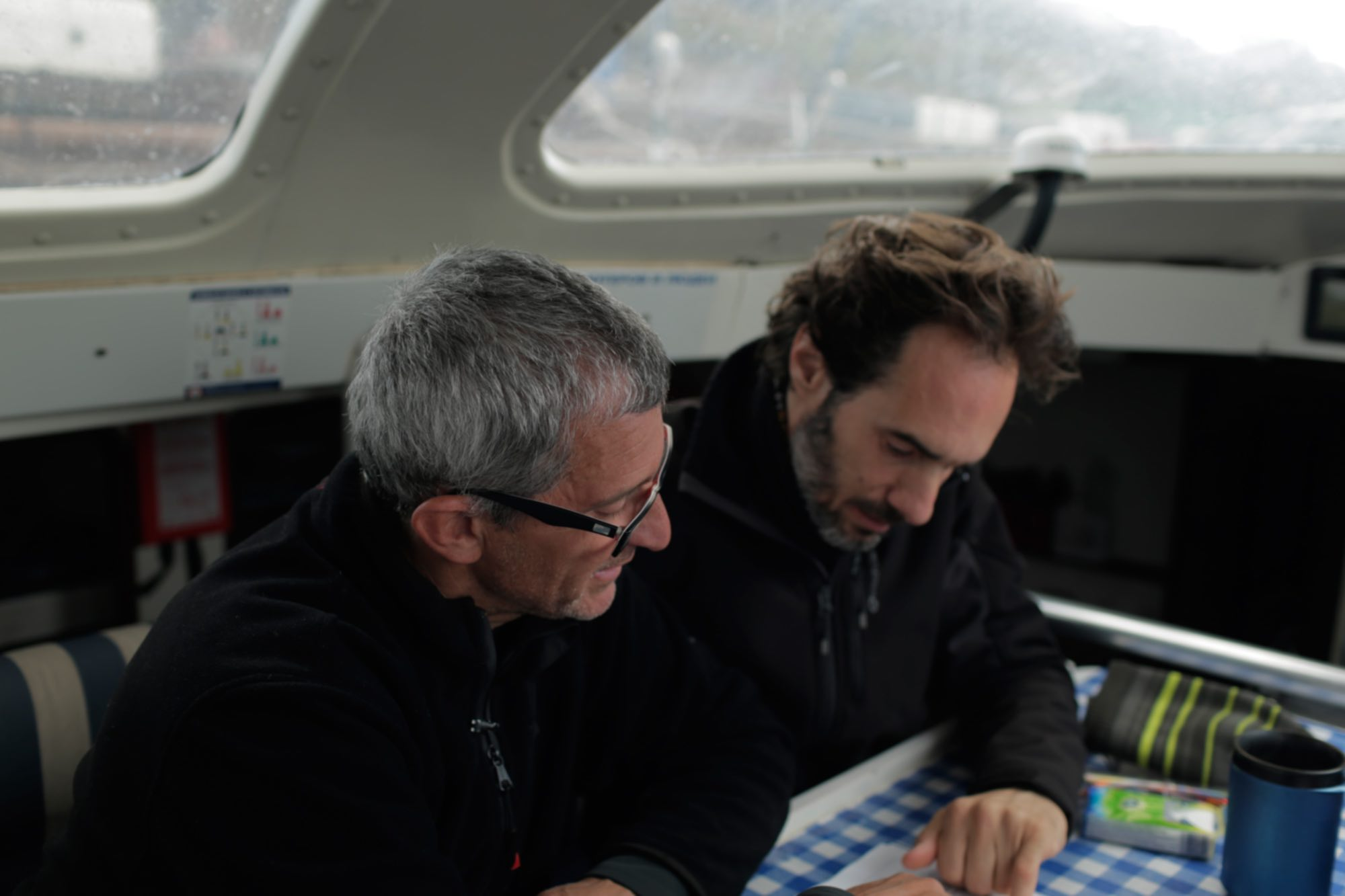 Albert Bargués observing a nautical chart together with the writer and scriptwriter Javier Argüello.
